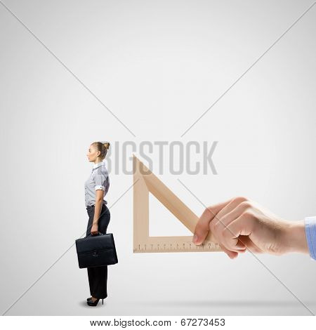 Businessman measuring miniature of business lady with ruler