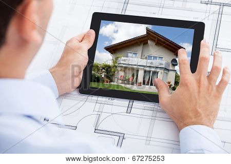 Architect Analyzing House On Digital Tablet Over Blueprint