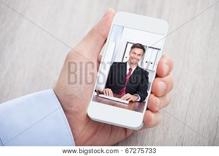 Businessman Video Conferencing With Colleague At Desk