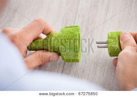 Businessman Holding Electric Plug And Socket At Desk