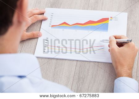 Businessman Analyzing Graph At Desk