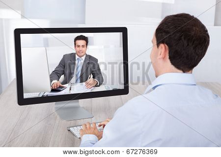 Businessman Video Conferencing With Coworker On Pc At Desk