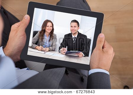 Businessman Video Conferencing With Colleagues On Digital Tablet
