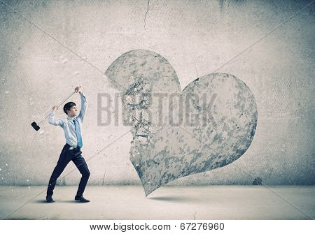 Aggressive businessman breaking stone heart with hammer