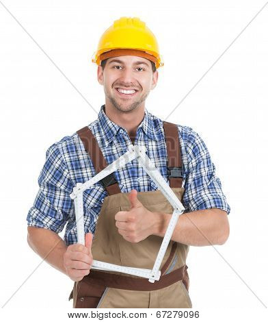 Confident Young Male Builder Holding House Frame