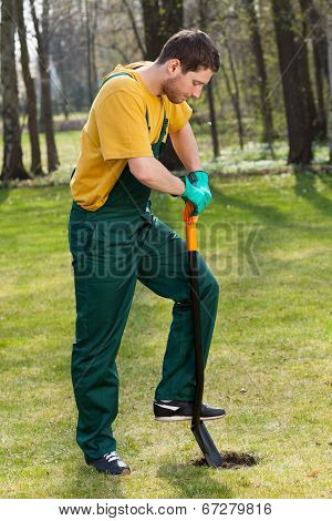 Man In Dungarees Digging In Garden