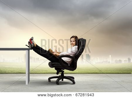 Young businesswoman sitting in chair with legs on table and reading book