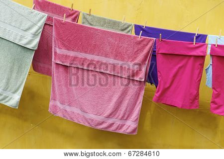 Closeup of a clothesline in a yellow facade.