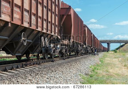 wagons of a freight train in motion go to horizon under bridge