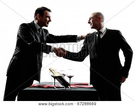 two businessmen dinning handshaking in silhouettes on white background