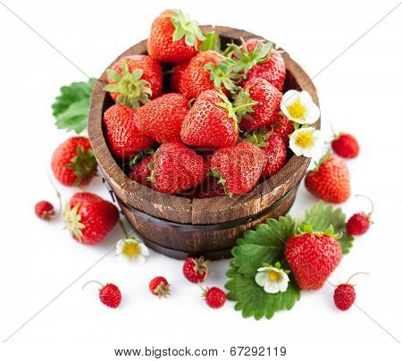 Fresh strawberry in wooden bucket with green leaf and flower. Isolated on white background