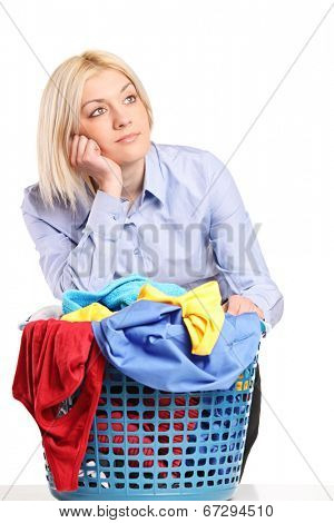 Bored woman leaning on a laundry basket isolated on white background
