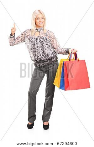 Full length portrait of a fashionable woman holding shopping bags and giving thumb up isolated on white background