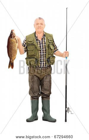 Full length portrait of a fisherman holding a fish and a fishing rod isolated on white background