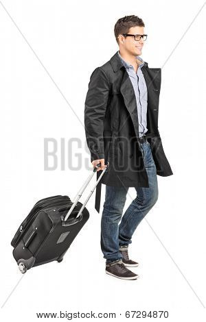 Handsome young man carrying his luggage isolated on white background