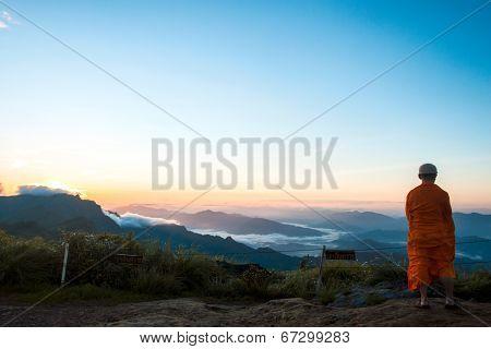 Monk Views Sunrise Scene At Phu Chi Fa In Chiangrai,thailand