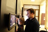 picture of realism  - Father with his son using touch screen in a museum - JPG