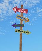 picture of nudism  - wooden four arrow direction signs post to the nude beach showers snacks and a lifeguard against a blue sky - JPG