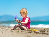 image of shoulder-blade  - baby girl playing in the sand with a shovel on the beach - JPG