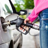 picture of gasoline station  - Closeup of woman pumping gasoline fuel in car at gas station - JPG