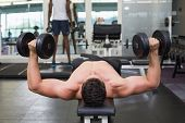 pic of work bench  - Shirtless bodybuilder lying on bench lifting heavy dumbbells at the gym - JPG