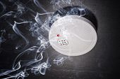 stock photo of fire insurance  - Smoke Detector in the smoke of a fire - JPG