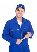 foto of overalls  - Portrait of young male mechanic in blue overalls holding spanner over white - JPG