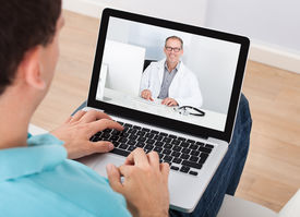 foto of chat  - Man having video chat with doctor on laptop at home - JPG