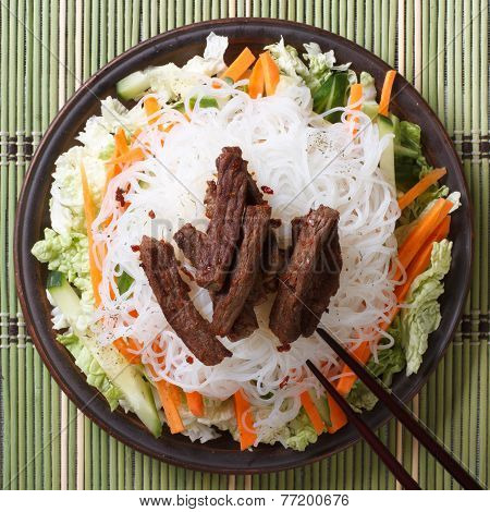Rice Noodles With Meat And Vegetables Close-up And Chopsticks