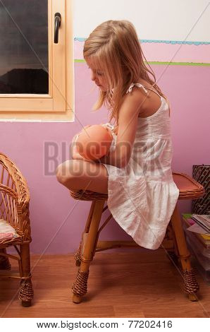 Sad lonely little girl sitting on small table in her room while holding baby toy
