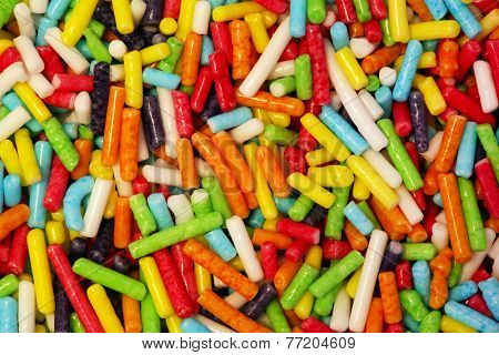 Colorful small sweet sugar sticks. Candy, cakes, cookies eatable decoration. Extreme close-up background, pattern.