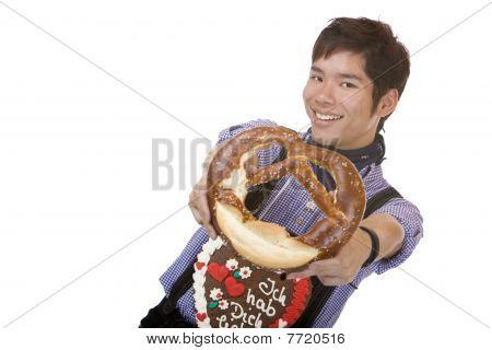 Asian Man In Lederhose Holds Oktoberfest Pretzel In Camera