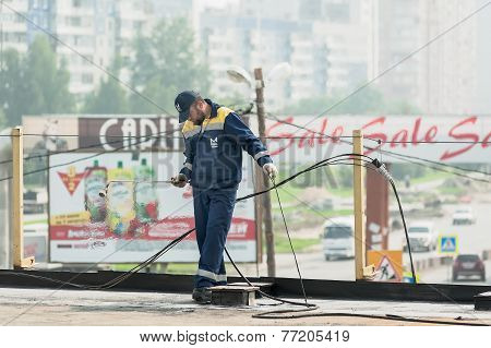 Worker holds a gas torch to waterproofing