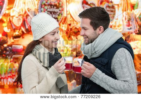 Romantic young couple drinking hot wine punch claret on christmas market