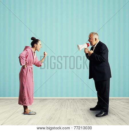 angry senior man in suit holding megaphone and screaming at dissatisfied woman in pink dressing gown. photo in the room