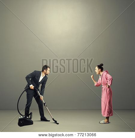 smiley man in suit holding vacuum cleaner and looking at screaming angry wife in pink dressing gown. photo in the grey room