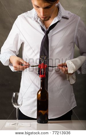 Man Opening Bottle Of Wine With Corkscrew