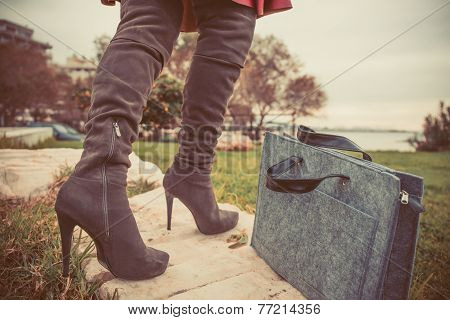 woman legs wearing boots and hand bag