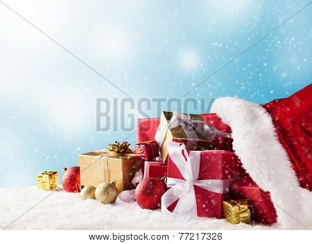Santa Claus bag full of gifts on snow with blur background