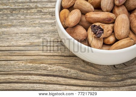 bowl of raw organic cacao beans  against grained wood