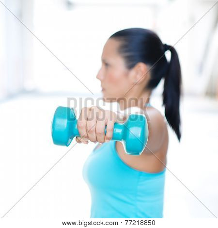 Closeup of hand with blue dumbbell of sporty woman doing triceps extension. Only hand and dumbbell in focus.