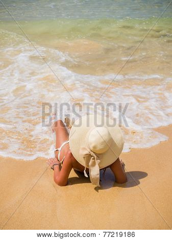 A sexy young woman or girl wearing a bikini and sun hat sitting on a deserted tropical beach in Thailand