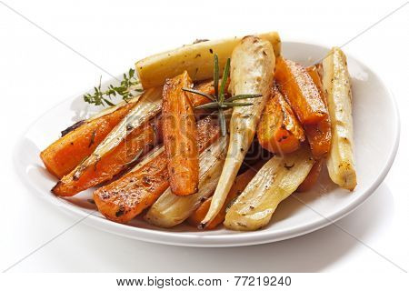 Roasted root vegetables in white dish, isolated.