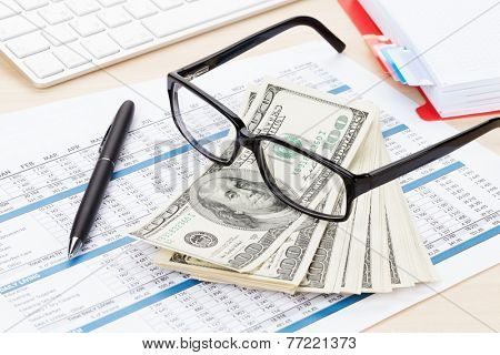 Office table with computer, supplies, reports and money cash