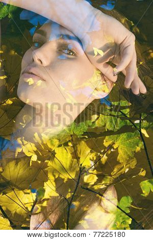 Double exposure portrait of young woman combined with photograph of nature