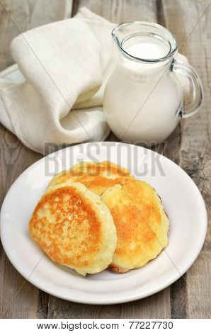 Fritters And Milk Jug On Rustic Table