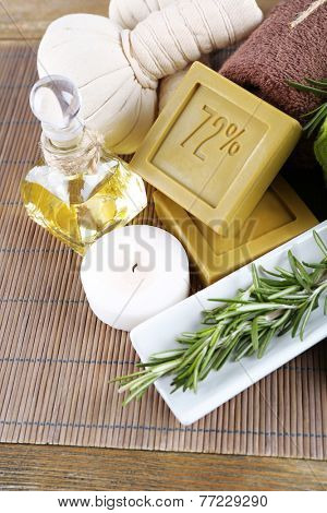 Handmade soap with the branches of rosemary, bottle with rosemary oil and towels, close-up. Rosemary spa concept