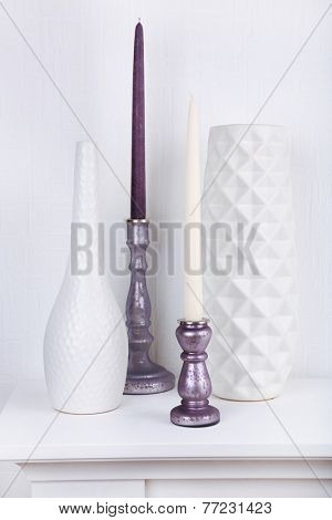 Candles in candle holders and vases on table on light background