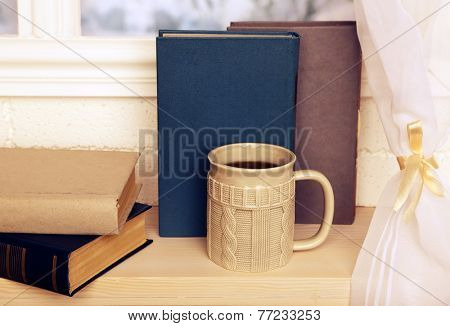 Old books and cup of coffee on windowsill