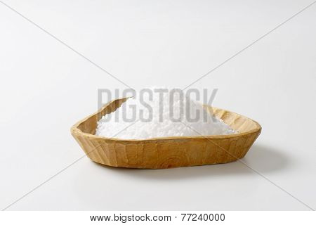 heap of coarse grained salt in the wooden handmade bowl